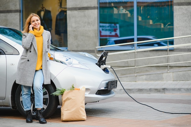 Mulher com telefone perto de um carro elétrico alugado