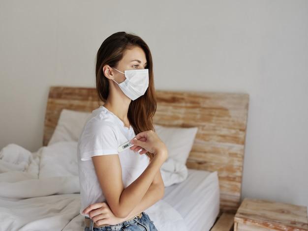 Mulher com termômetro debaixo da máscara médica do braço. foto de alta qualidade