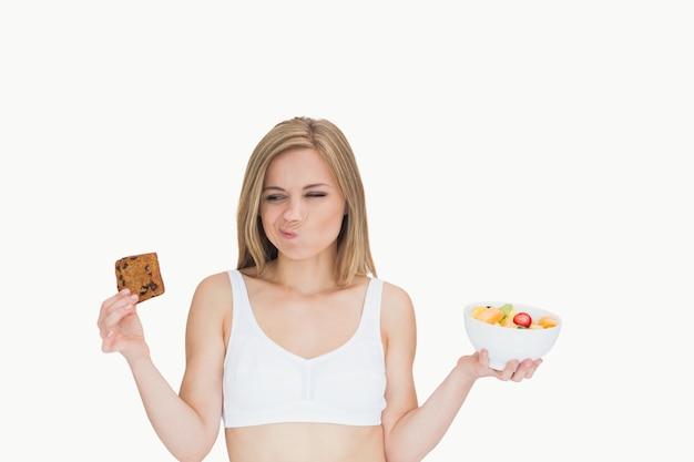 Mulher com tigela de frutas fazendo rostos enquanto olha para o biscoito