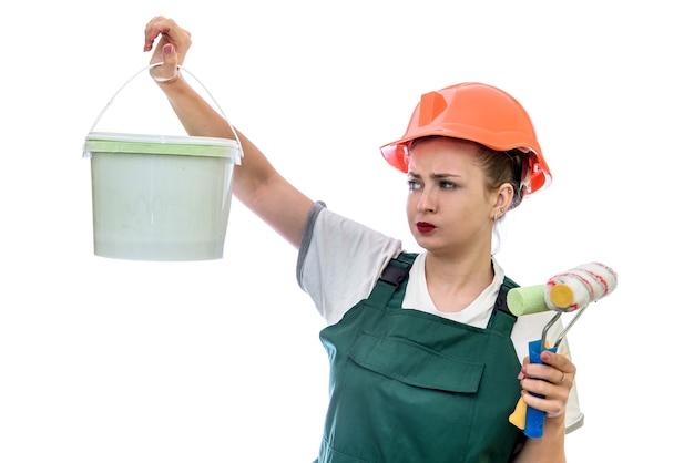 Mulher com tinta em um balde e ferramentas isoladas em branco