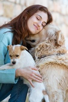 Mulher com tiro médio abraçando cachorros