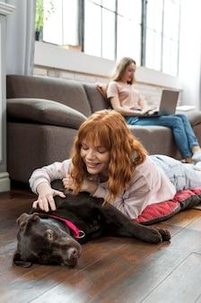 Mulher com tiro médio acariciando cachorro no chão