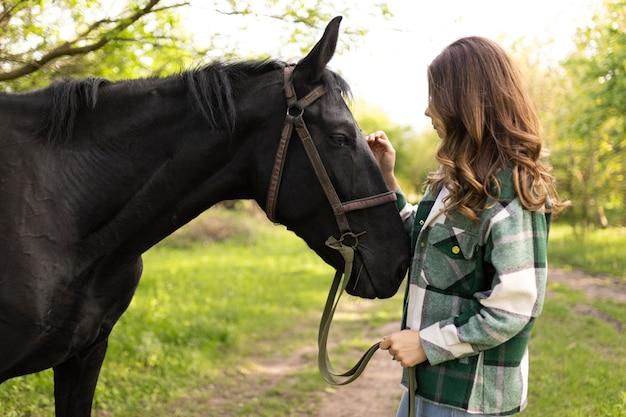 Mulher com tiro médio acariciando o cavalo