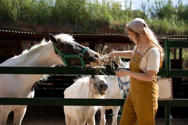 Mulher com tiro médio alimentando animais