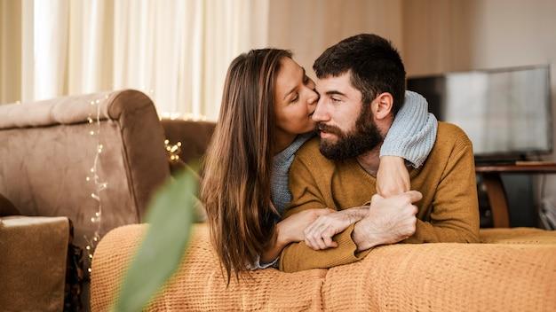 Mulher com tiro médio beijando homem na bochecha