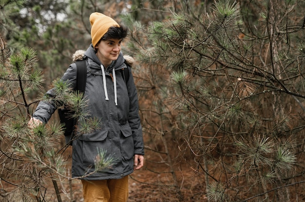 Mulher com tiro médio caminhando na floresta