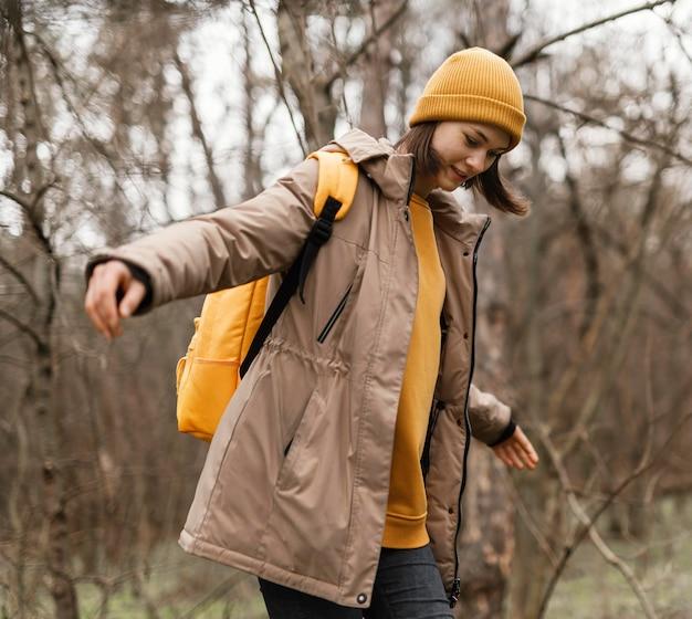 Mulher com tiro médio caminhando pela floresta