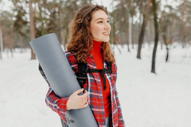 Mulher com tiro médio carregando tapete