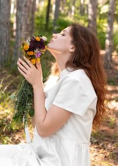Mulher com tiro médio cheirando flores