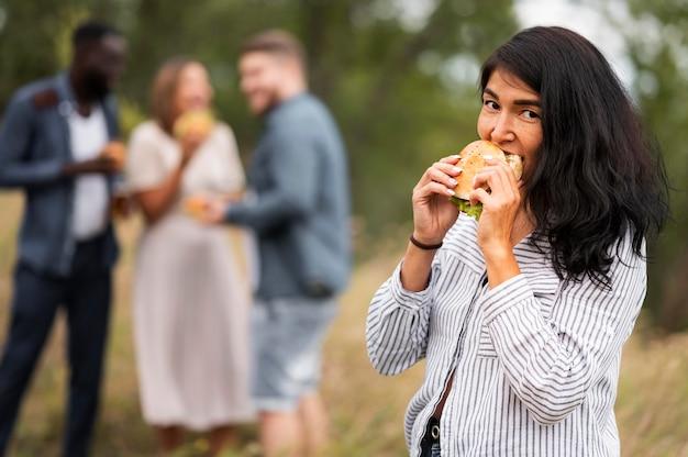 Mulher com tiro médio comendo hambúrguer