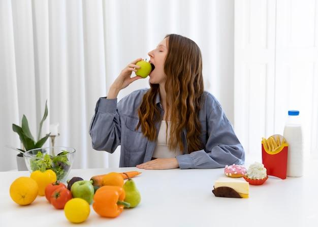 Mulher com tiro médio comendo maçã