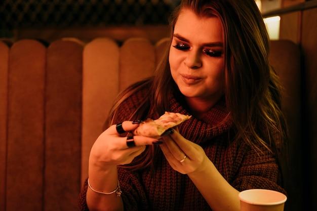 Mulher com tiro médio comendo pizza