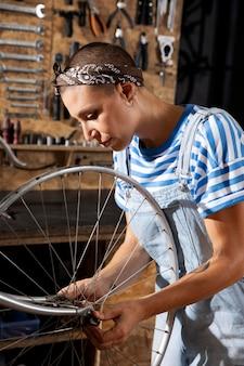 Mulher com tiro médio consertando bicicleta