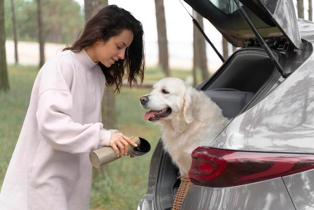 Mulher com tiro médio dando água para cachorro