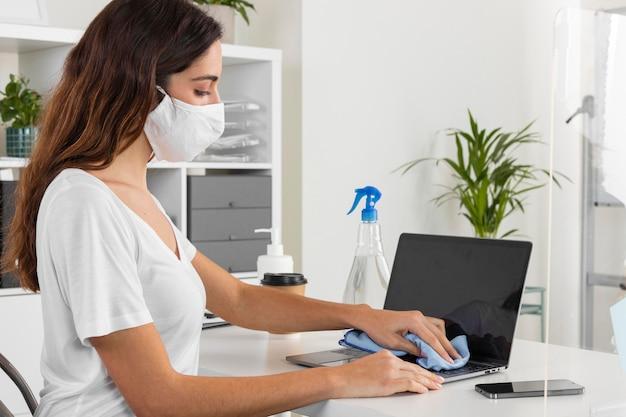Mulher com tiro médio desinfetando laptop