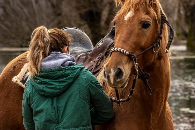 Mulher com tiro médio e cavalo do lado de fora