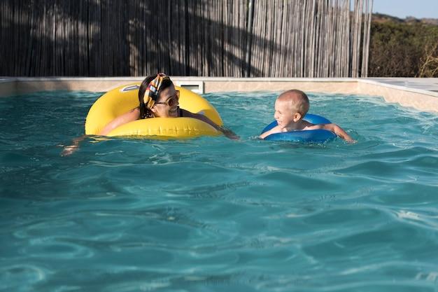 Mulher com tiro médio e criança na piscina