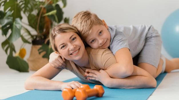 Mulher com tiro médio e criança no tapete de ioga