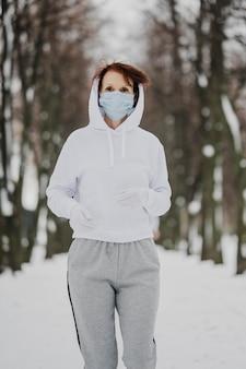 Mulher com tiro médio e máscara correndo