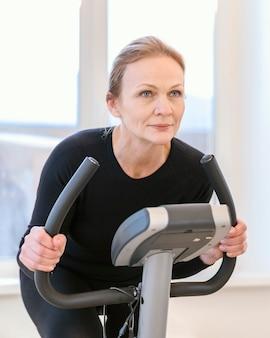 Mulher com tiro médio em bicicleta giratória