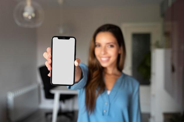 Mulher com tiro médio embaçado segurando o telefone