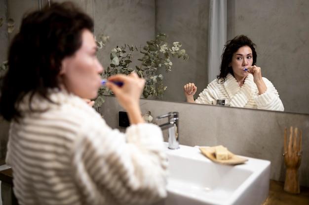 Mulher com tiro médio escovando os dentes
