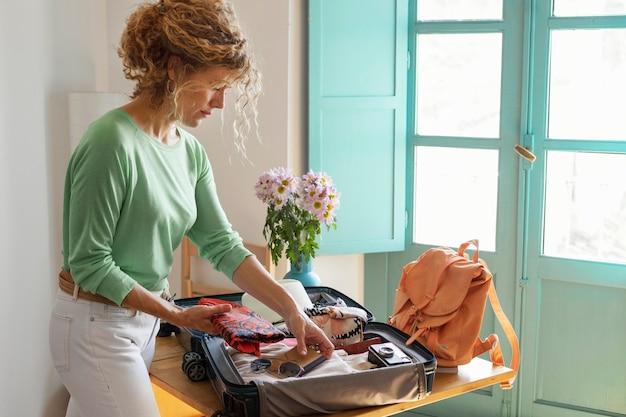 Mulher com tiro médio fazendo as malas