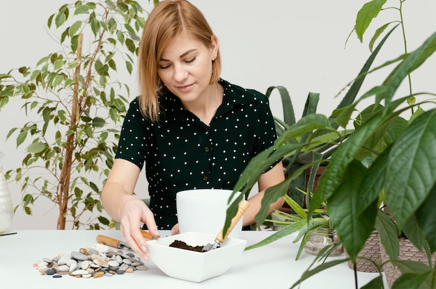 Mulher com tiro médio fazendo jardinagem dentro de casa