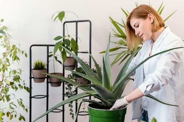 Mulher com tiro médio fazendo jardinagem