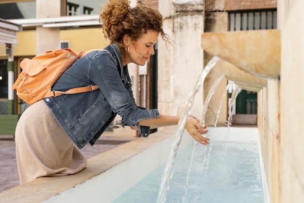 Mulher com tiro médio lavando as mãos