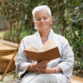 Mulher com tiro médio lendo ao ar livre