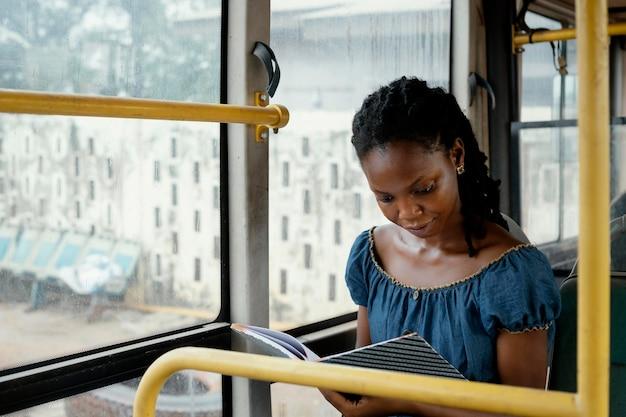 Mulher com tiro médio lendo no ônibus