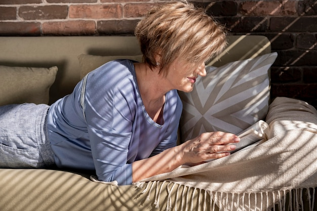 Mulher com tiro médio lendo no sofá