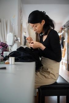 Mulher com tiro médio na cadeira costurando