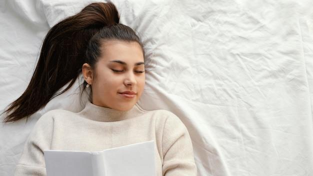 Mulher com tiro médio na cama com livro