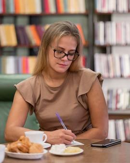 Mulher com tiro médio na escrita da biblioteca