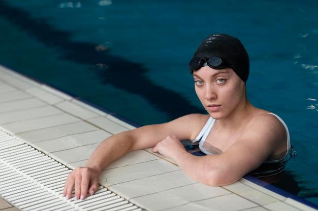 Mulher com tiro médio na piscina com óculos de proteção