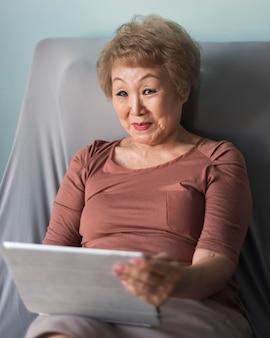 Mulher com tiro médio no sofá segurando o tablet