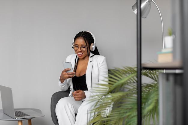 Mulher com tiro médio no trabalho com telefone