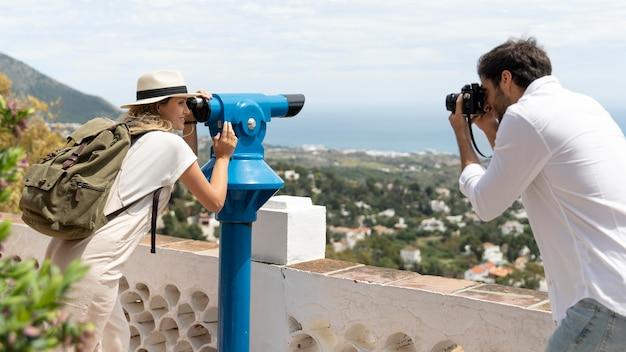 Mulher com tiro médio olhando pelo telescópio