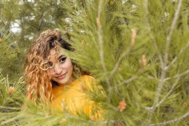 Mulher com tiro médio perto de árvore