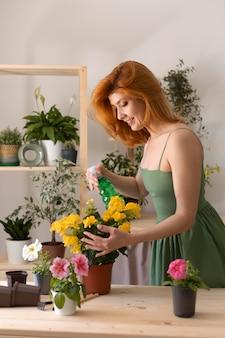 Mulher com tiro médio regando flor