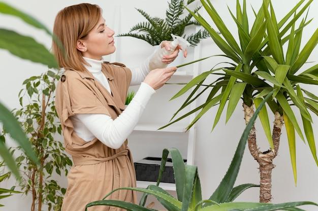 Mulher com tiro médio regando folhas