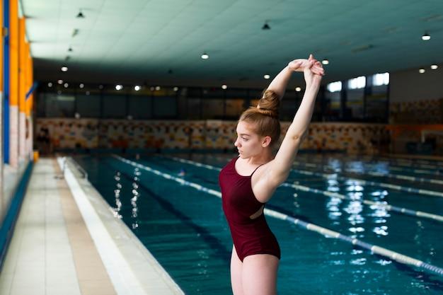 Mulher com tiro médio se alongando perto da piscina