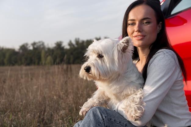 Mulher com tiro médio segurando cachorro ao ar livre