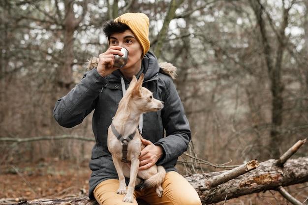 Mulher com tiro médio segurando cachorro na floresta