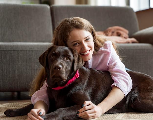Mulher com tiro médio segurando cachorro