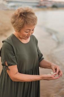 Mulher com tiro médio segurando conchas