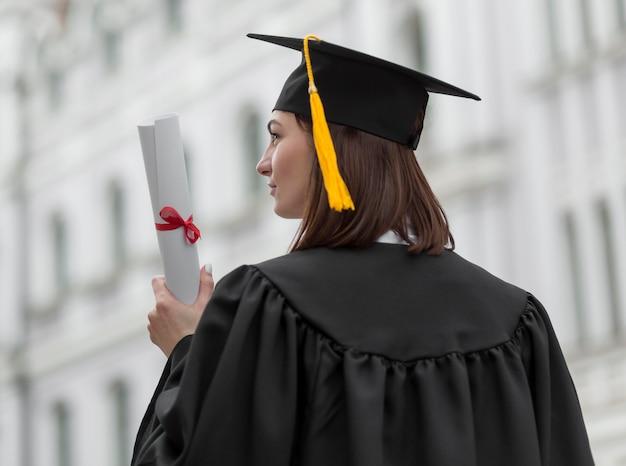 Mulher com tiro médio segurando diploma