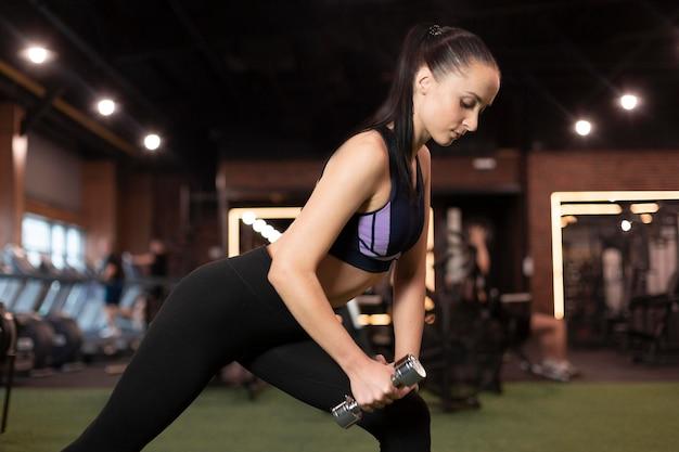 Mulher com tiro médio segurando halteres